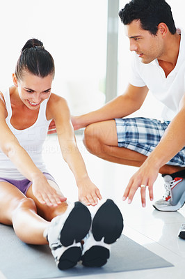 Buy stock photo Smiling woman doing stretching exercise assisted by fitness trainer