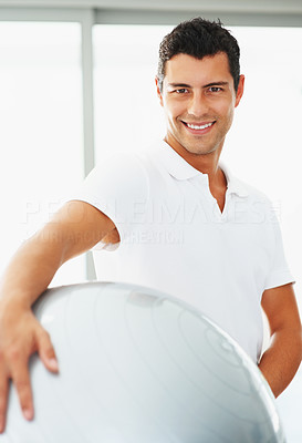 Buy stock photo Portrait of young man posing with exercise ball