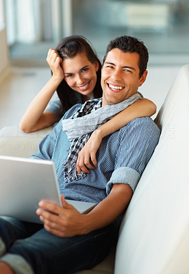 Buy stock photo Young couple relaxing at home while on the laptop