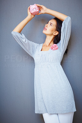 Buy stock photo Young woman checking her piggy bank for money