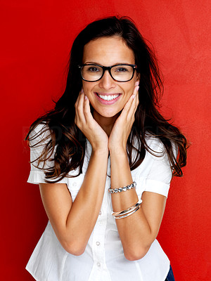 Buy stock photo Portrait of smiling young woman wearing glasses against red background
