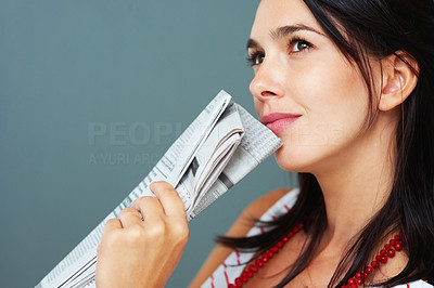 Buy stock photo Thoughtful pretty woman holding newspaper and looking up