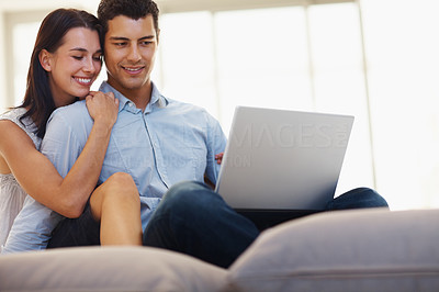 Buy stock photo Young loving couple using laptop at home