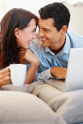 Buy stock photo Loving young couple with laptop looking at each other