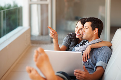 Buy stock photo Young woman showing something to her boyfriend while working on laptop