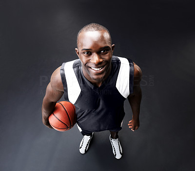 Buy stock photo High angle of a happy young man holding a basketball looking up
