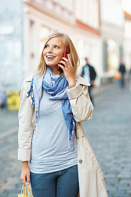 Buy stock photo Young woman with shopping bags and talking on mobile phone