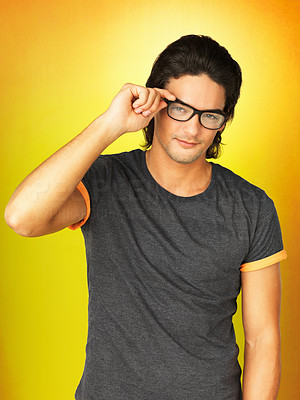 Buy stock photo Attractive man adjusting glasses on face against yellow background
