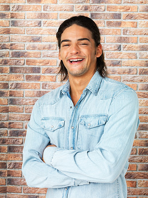 Buy stock photo Attractive man smiling against brick wall with his arms folded