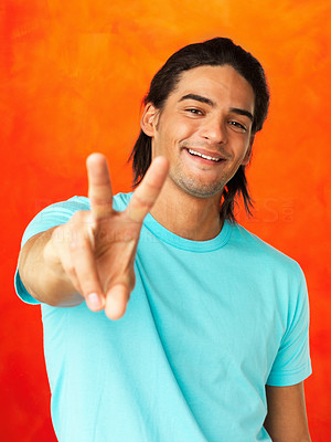 Buy stock photo Handsome man giving peace sign on orange background