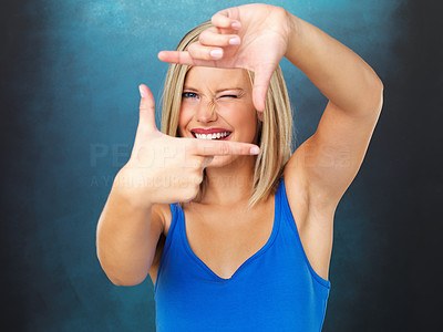 Buy stock photo Pretty woman making a frame with her fingers, squinting with one eye closed