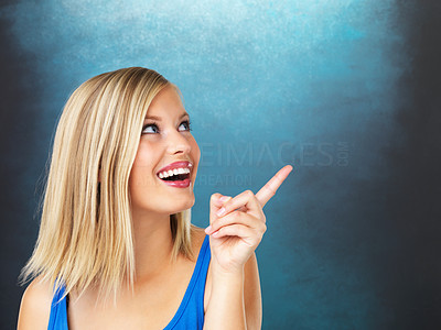 Buy stock photo Closeup portrait of pretty woman pointing upward at copyspace