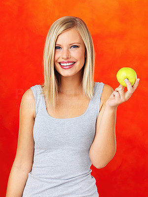 Buy stock photo Smiling woman holding green apple on orange background