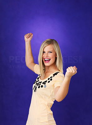 Buy stock photo Excited young woman cheering with fists clenched