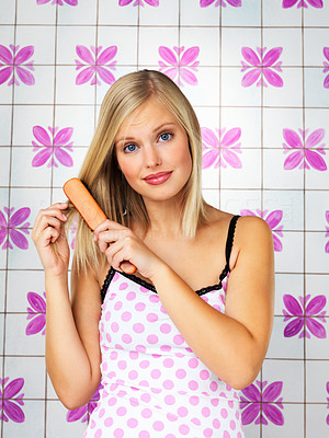 Buy stock photo Pretty woman looking concerned while brushing her hair