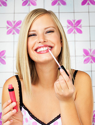 Buy stock photo Pretty woman putting on lip gloss indoors