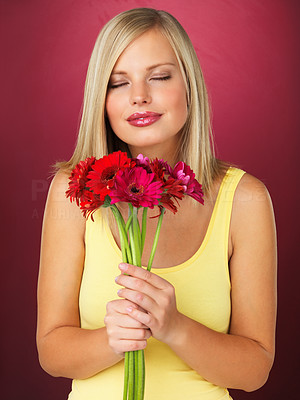 Buy stock photo Attractive blonde woman smelling bouquet of daisies