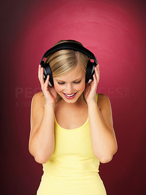 Buy stock photo Pretty blonde woman looking down with headphones on