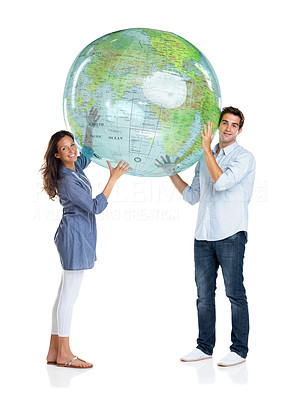 Buy stock photo Portrait of a beautiful young couple holding a globe above head over white background