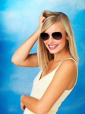 Buy stock photo Side view of flirtatious woman wearing sunglasses against blue background