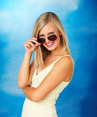 Buy stock photo Side view of flirtatious woman looking over her sunglasses