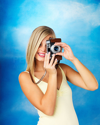 Buy stock photo Pretty woman smiling while taking a photo with a vintage camera against a blue background