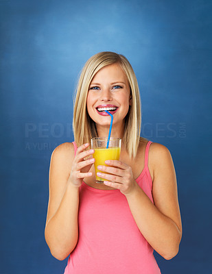 Buy stock photo Pretty woman sipping orange juice against blue background