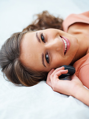 Buy stock photo Young girl lying on bed smiling with phone and looking to the side