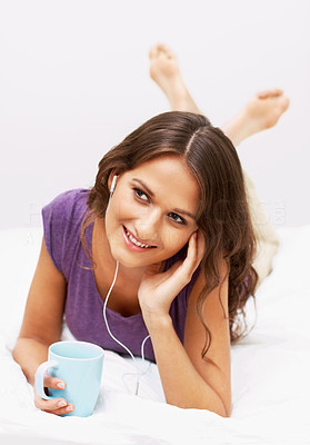 Buy stock photo Girl listening to music on bed while enjoying cup of coffee