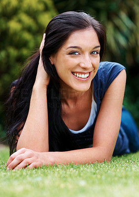 Buy stock photo Portrait of a cute young woman relaxing on the grass in the park - Outdoor