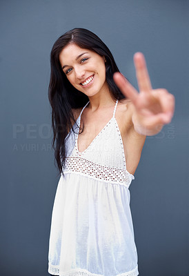 Buy stock photo Portrait of a beautiful young girl showing sign of victory against grey background