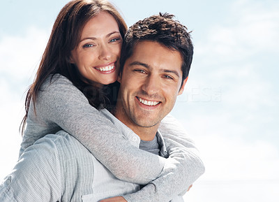 Buy stock photo Portrait of a handsome young man giving a piggyback ride to his girlfriend - Outdoor