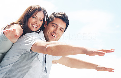 Buy stock photo Handsome young man carrying his girlfriend on his back with their hands outstretched