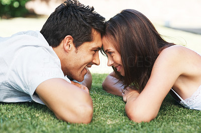 Buy stock photo Portrait of a beautiful young couple lying head to head on grass - Outdoor