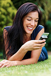 Young woman reading a funny sms on cellphone
