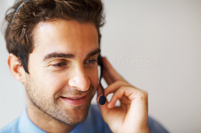 Buy stock photo Closeup portrait of smiling young executive with headset looking away - copyspace