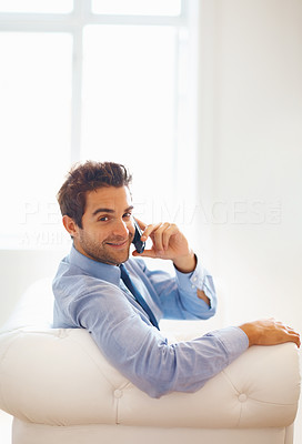 Buy stock photo Side view of happy executive sitting on sofa while on phone