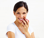 Beautiful young woman eating an apple isolated over white