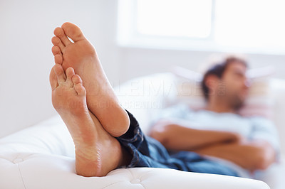Buy stock photo Focus on feet of man lying down on bed