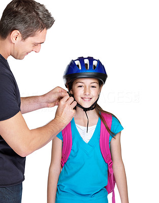 Buy stock photo Portrait of a young man tying helmet on his daughter head against white background