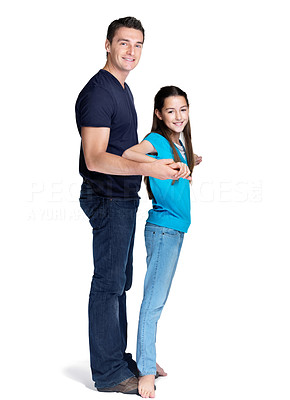 Buy stock photo Portrait of a sweet young girl standing on her father feet while dancing over white background