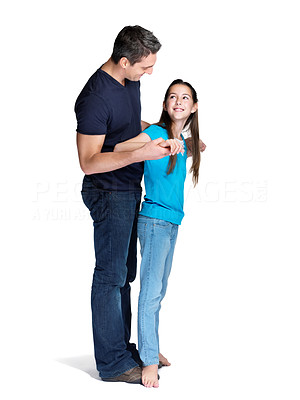 Buy stock photo Portrait of a cute little girl standing on her father feet while dancing over white background