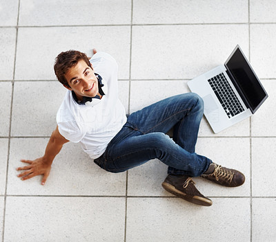 Buy stock photo Relaxed young man sitting on floor and looking up with a laptop - Top view