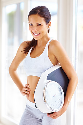 Buy stock photo Portrait of cheerful young woman holding a weight scale
