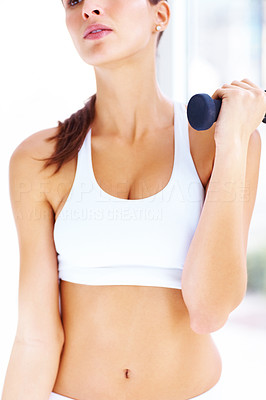 Buy stock photo Cropped image of beautiful young woman working out with free weights