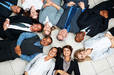 Buy stock photo Top view of smiling business people lying on floor