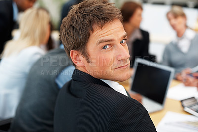 Buy stock photo Serious business man looking at you with colleagues in background