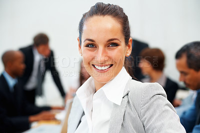 Buy stock photo Closeup of pretty executive with colleagues in background