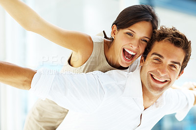 Buy stock photo Handsome young man carrying his girlfriend on his back with their arms outstretched