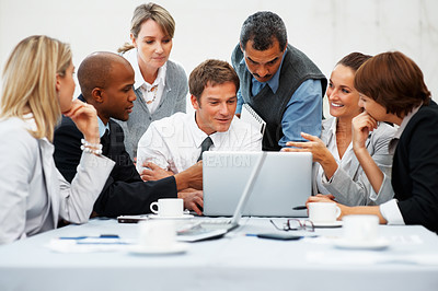 Buy stock photo Businesspeople sitting around a laptop computer during meeting